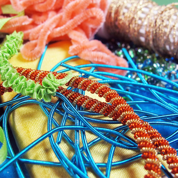 Fabric, ribbon, beads and specialty threads help add dimension and texture to embroidery.