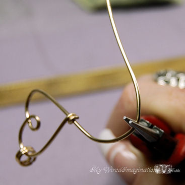 once you have curve in the second heart started, use round nose pliers to form the loop in the bottom heart
