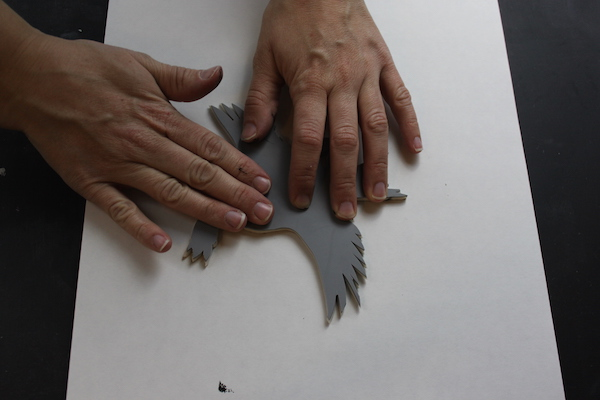 Pressing bird stamp on paper