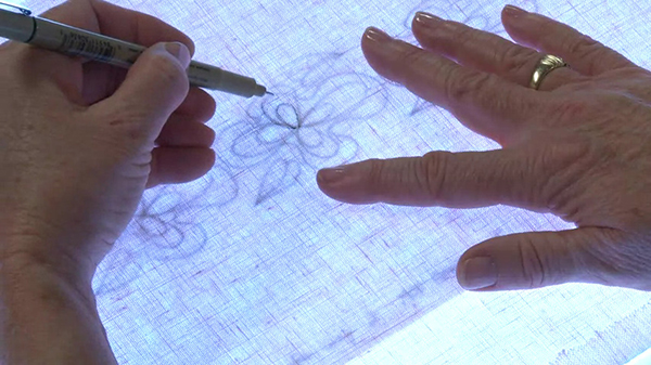 Tracing embroidery designs on fabric.