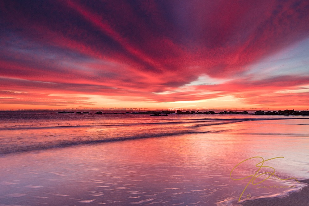 Fiery skies reflected in the wet sand at Hampton Beach, NH