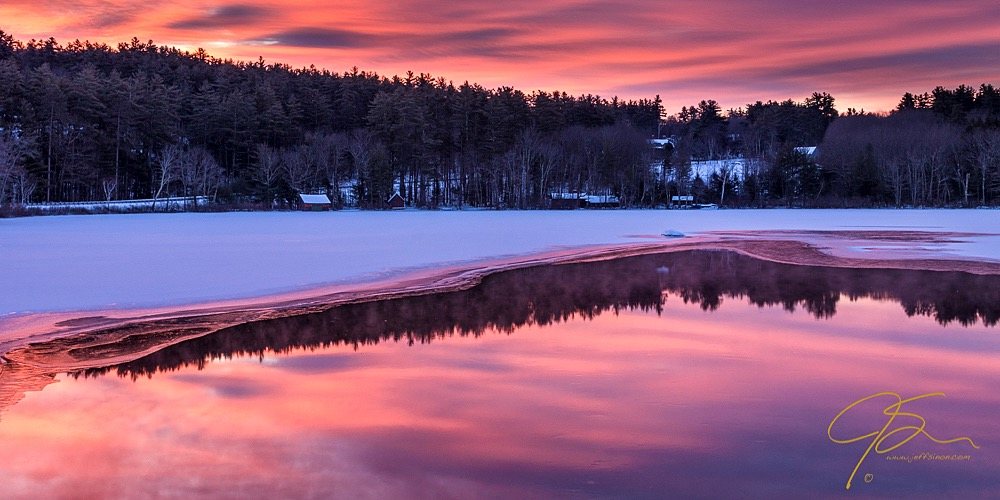 Warm fiery sunrise sky over partially frozen Little Lake, Tamworth, NH