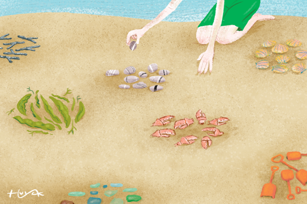 A child collects clusters of objects from the beach