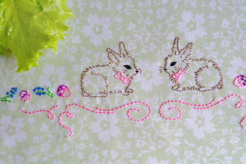 hand embroidered bunnies in brown on green floral cloth