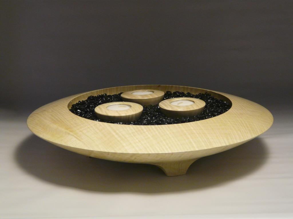 wooden bowl with black rocks and 3 candles in it