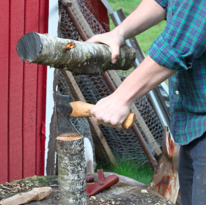 hatchet in the center of log over the pith (dark center), striking the hatchet with a mallet or another branch