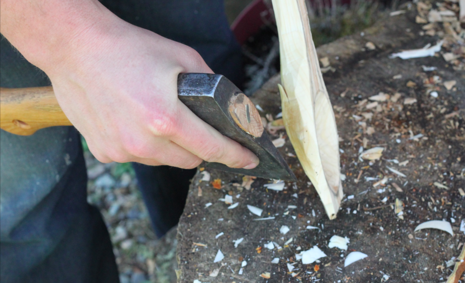 rough shaping the bowl of the spoon with a hatchet