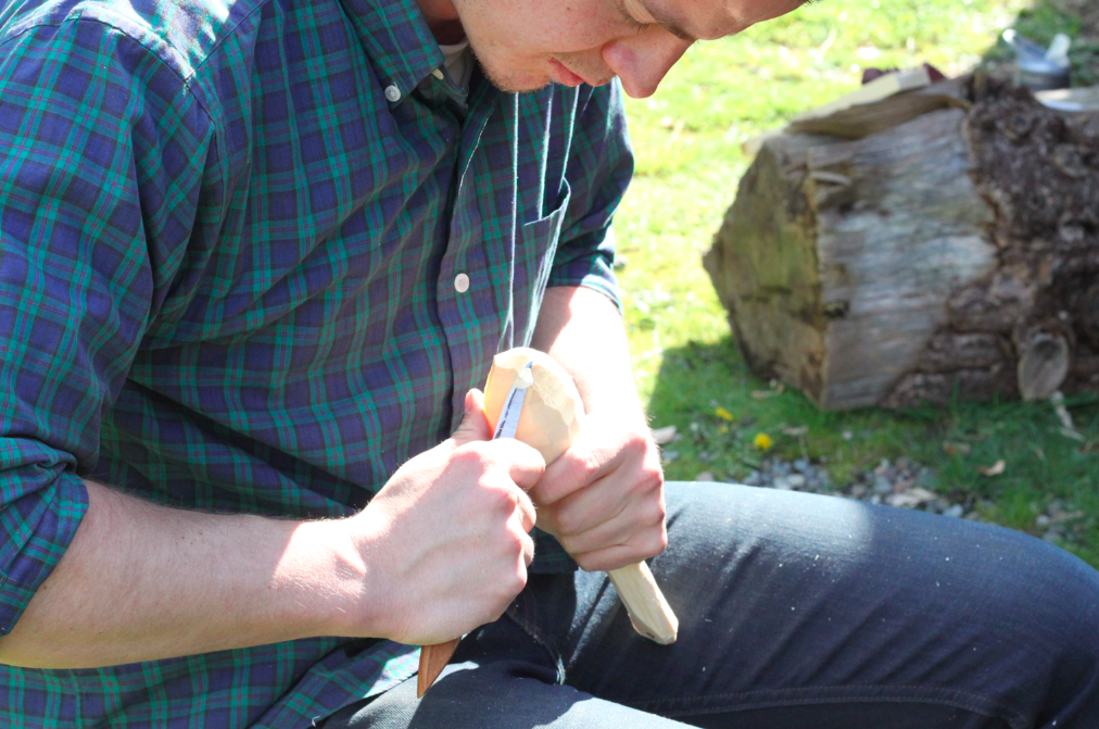 finishing refining the shape of the spoon with a carving knife