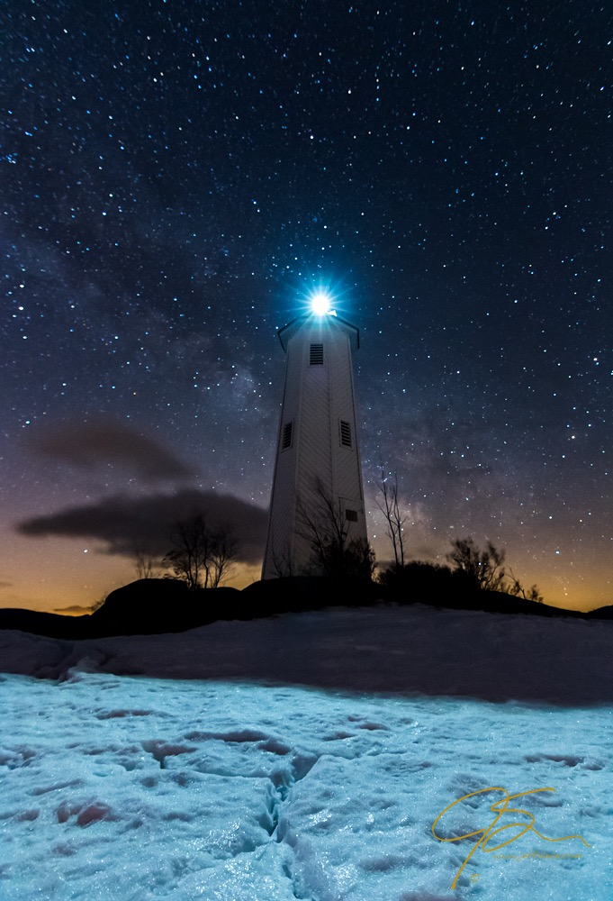 Loon Island Lighthouse un frozen Lake Sunappe in New Hampshire under the Milky Way