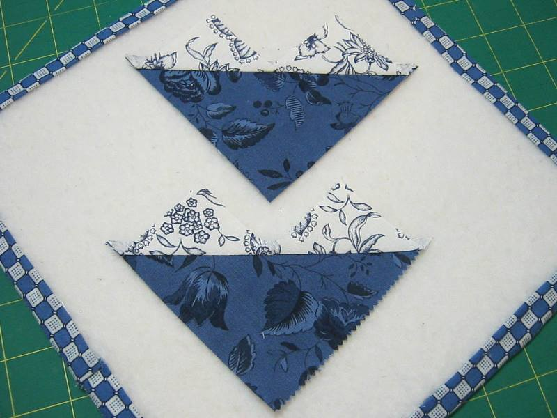 two halves of sewn together fabric squares with smaller squares pressed up