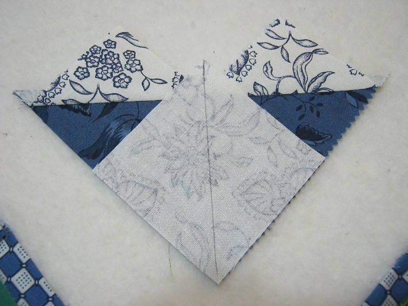 smaller fabric square with drawn on diagonal line on top of sewn together half square