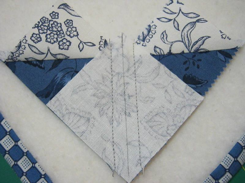 smaller fabric square sewn onto larger square a quarter inch from drawn on diagonal line