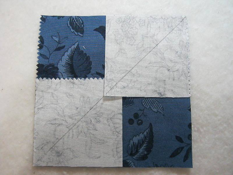 A large square fabric block with two smaller fabric blocks with a diagonal line drawn across them on top