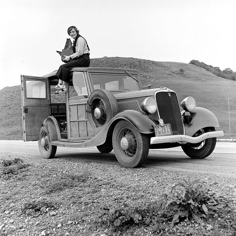 Dorothea Lange sitting on a car