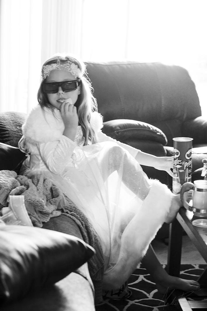 Girl playing dress up eating chip