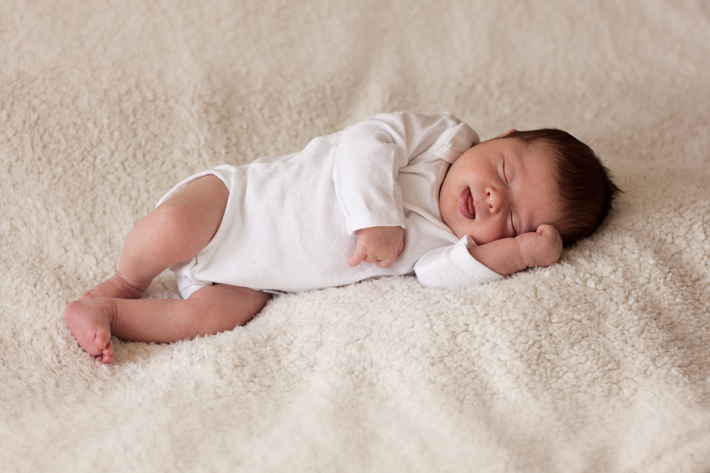 Newborn baby photographed on off-white backdrop