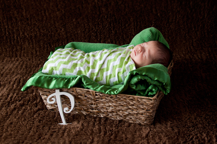 Newborn photography props shown including basket, wooden letters, and backdrop
