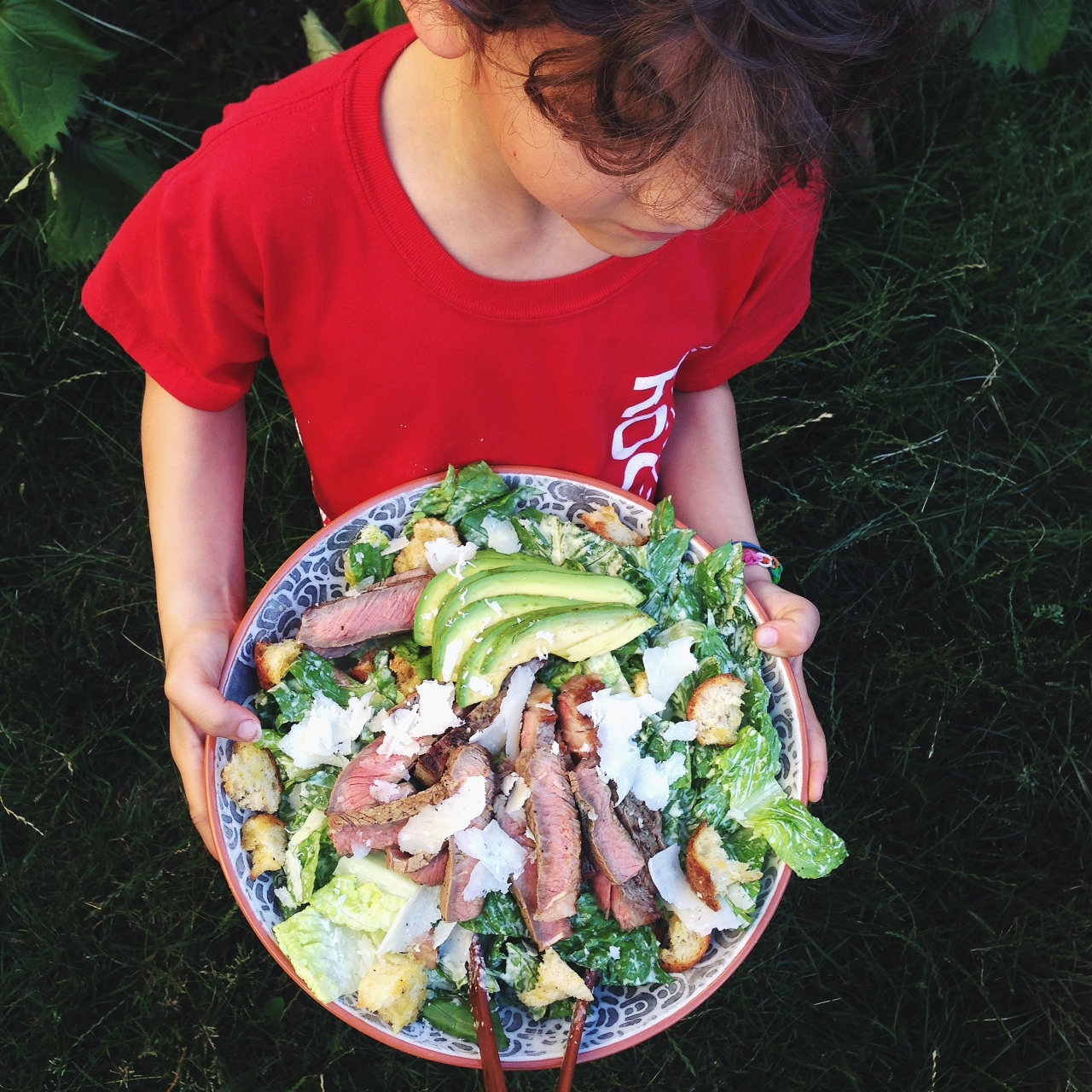 Boy holding a bowl of caesar salad