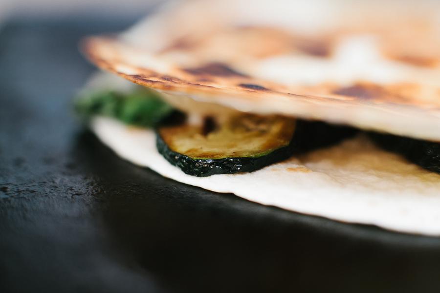 A close up of a zucchini, basil and gruyere quesadilla