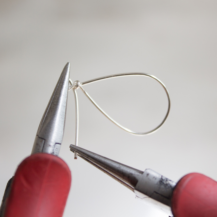 Hold the smaller loop firmly with your flat-nose pliers