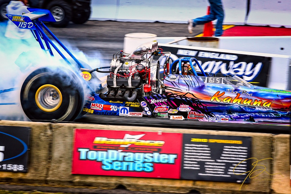 A dragster at New England Dragway violently spins its tires as it launches from the starting line.