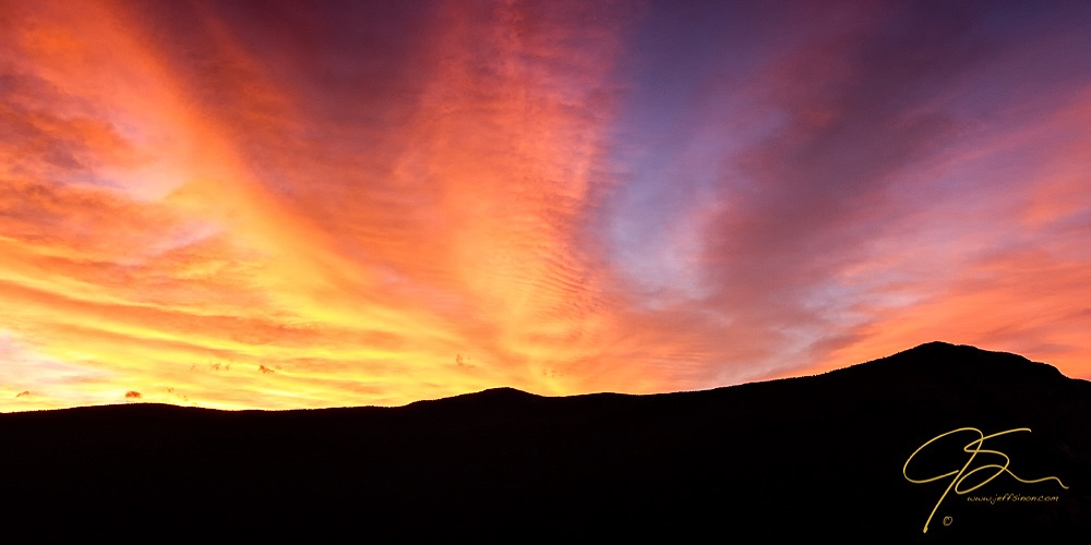 Fiery sky over the black silhouette of mountains.