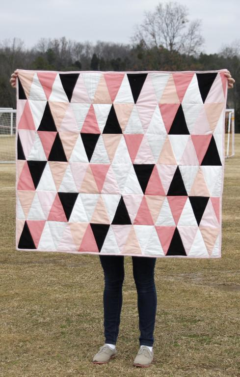 Woman holding a pink triangle baby quilt