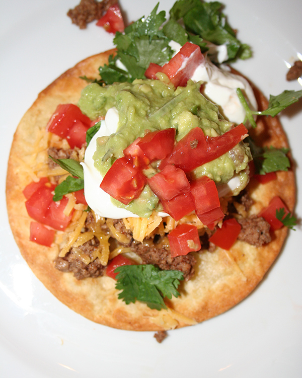 Tostada topped with tomatoes, sour cream, cilantro and tomatoes