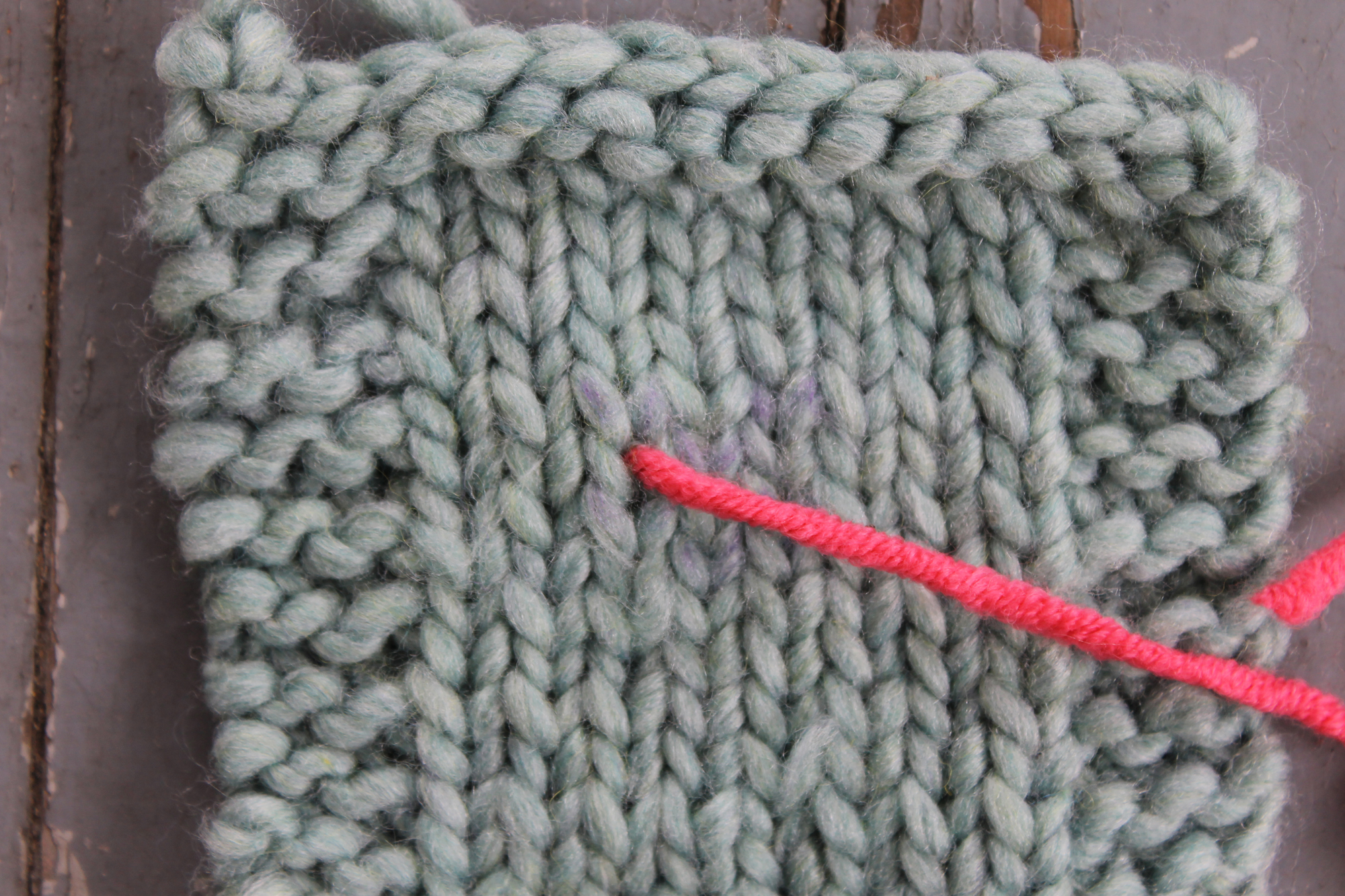 Inserting the tapestry needle at the bottom of the V for duplicate stitch