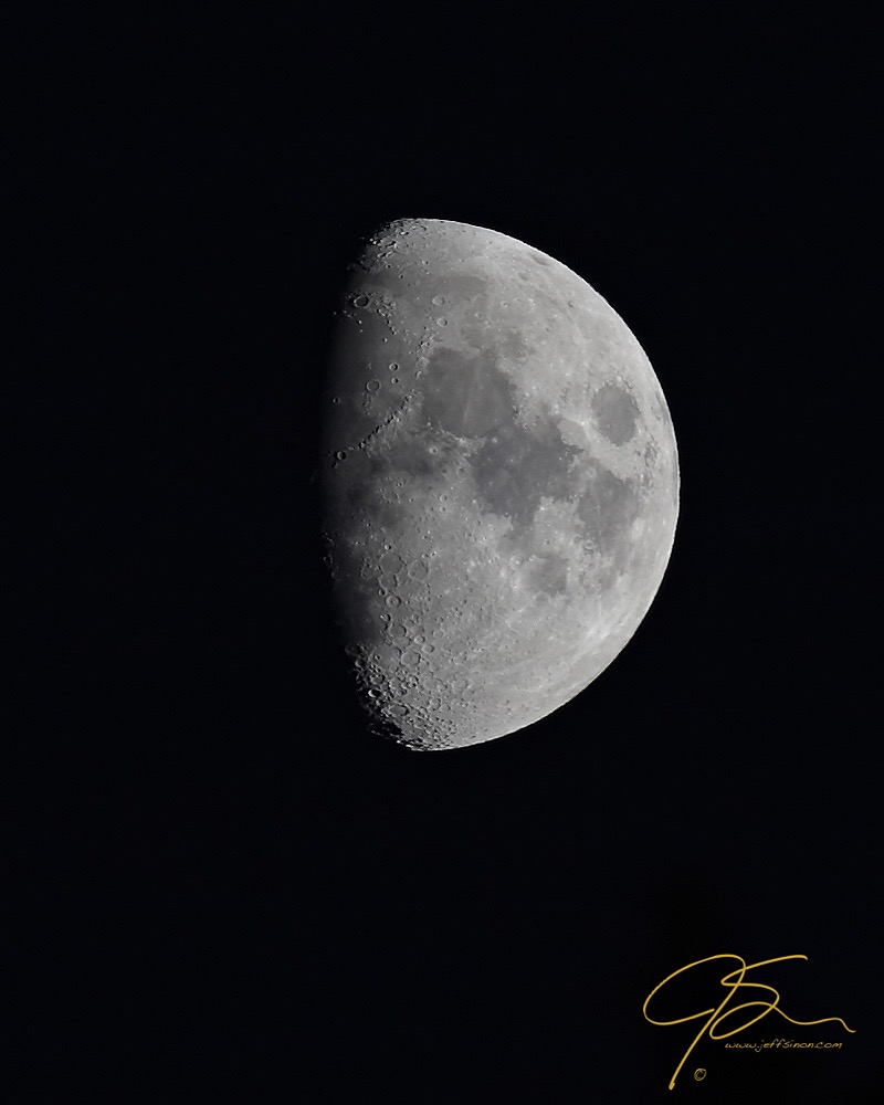 three quarter moon in the dark night sky