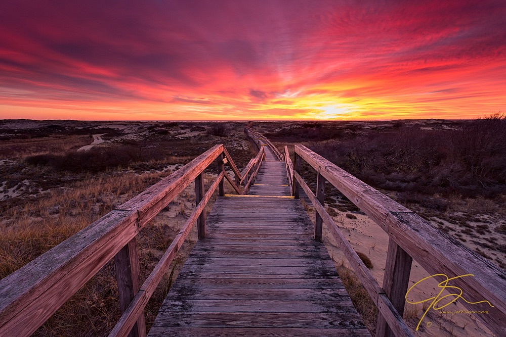 A weathered boardwalk winds through the sand dunes towards the ocean and a fiery sunrise.