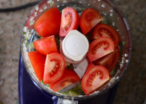 Adding tomatoes to food processor salsa