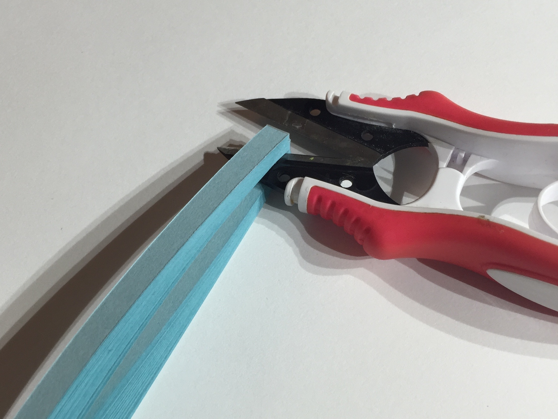 Image of scissors cutting quilling strip set in half for hanging