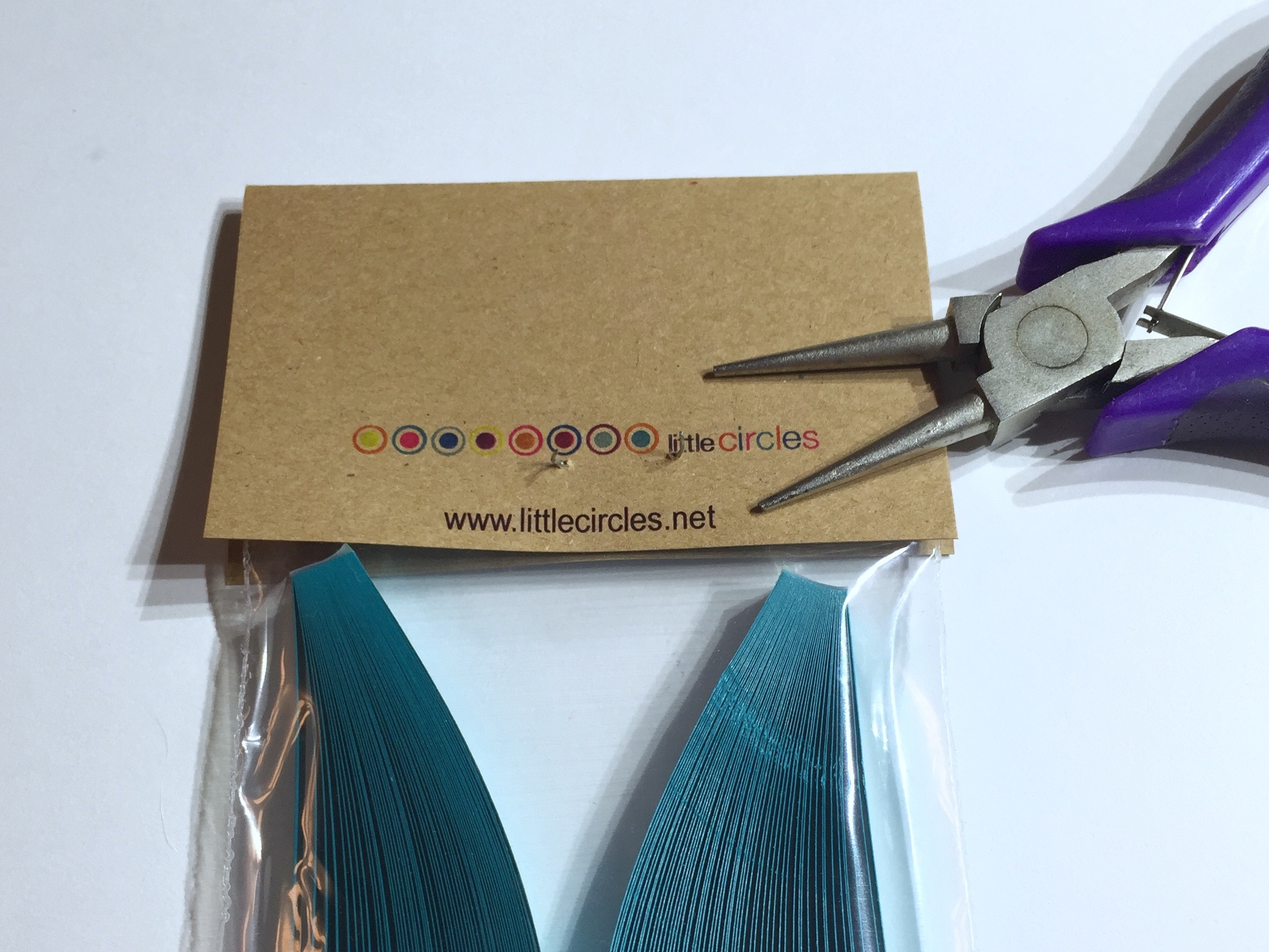 Image of taking staple out of a pack pf quilling strips lablel