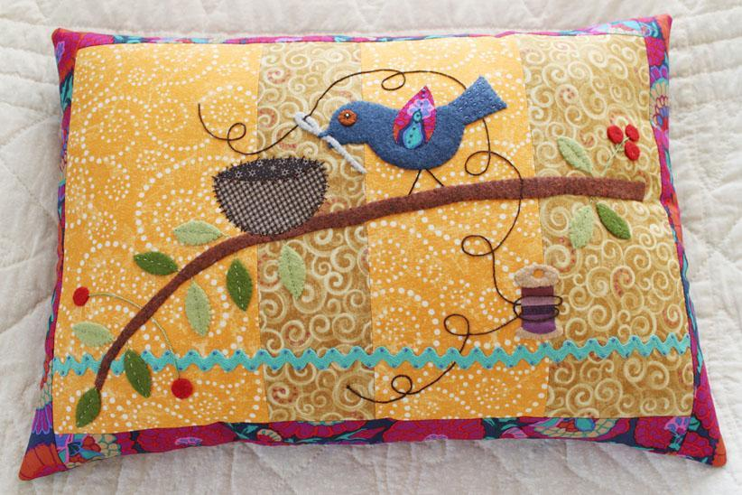 bird on a quilted pillow