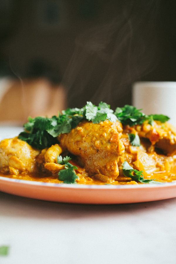 Steaming plate of butter chicken topped with fresh cilantro