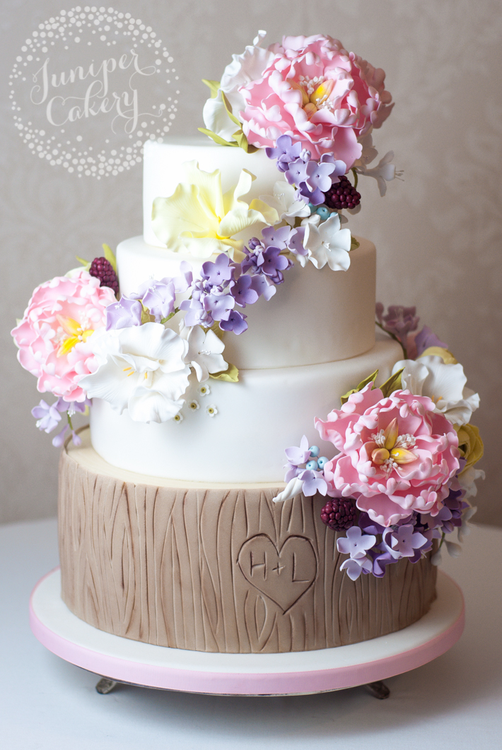 Floral garland wedding design with tree bark cake base by Juniper Cakery
