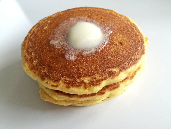 A delicious stack of cornbread pancakes with a pat of melty butter — yum!
