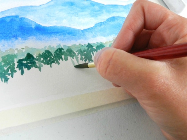 Small watercolor trees add scale to a mountain painting