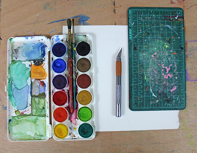 watercolor supplies and knife for cut out art