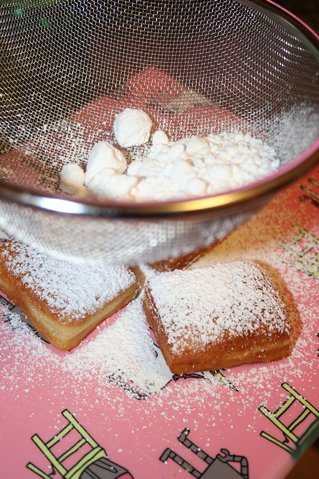 Beignets being dusted with sugar