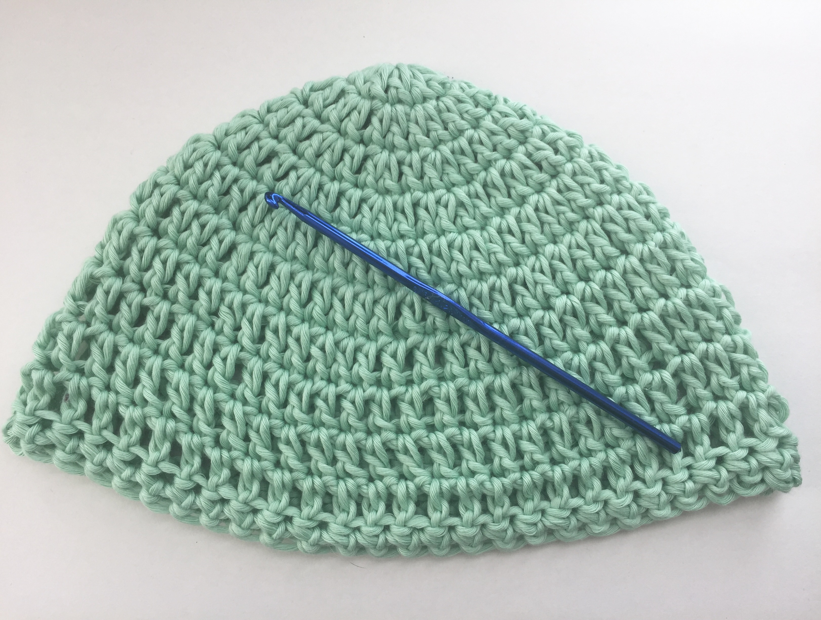 Green Crocheted Baby Hat With a Blue Crochet Hook