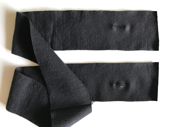 Black strip with two buttonholes