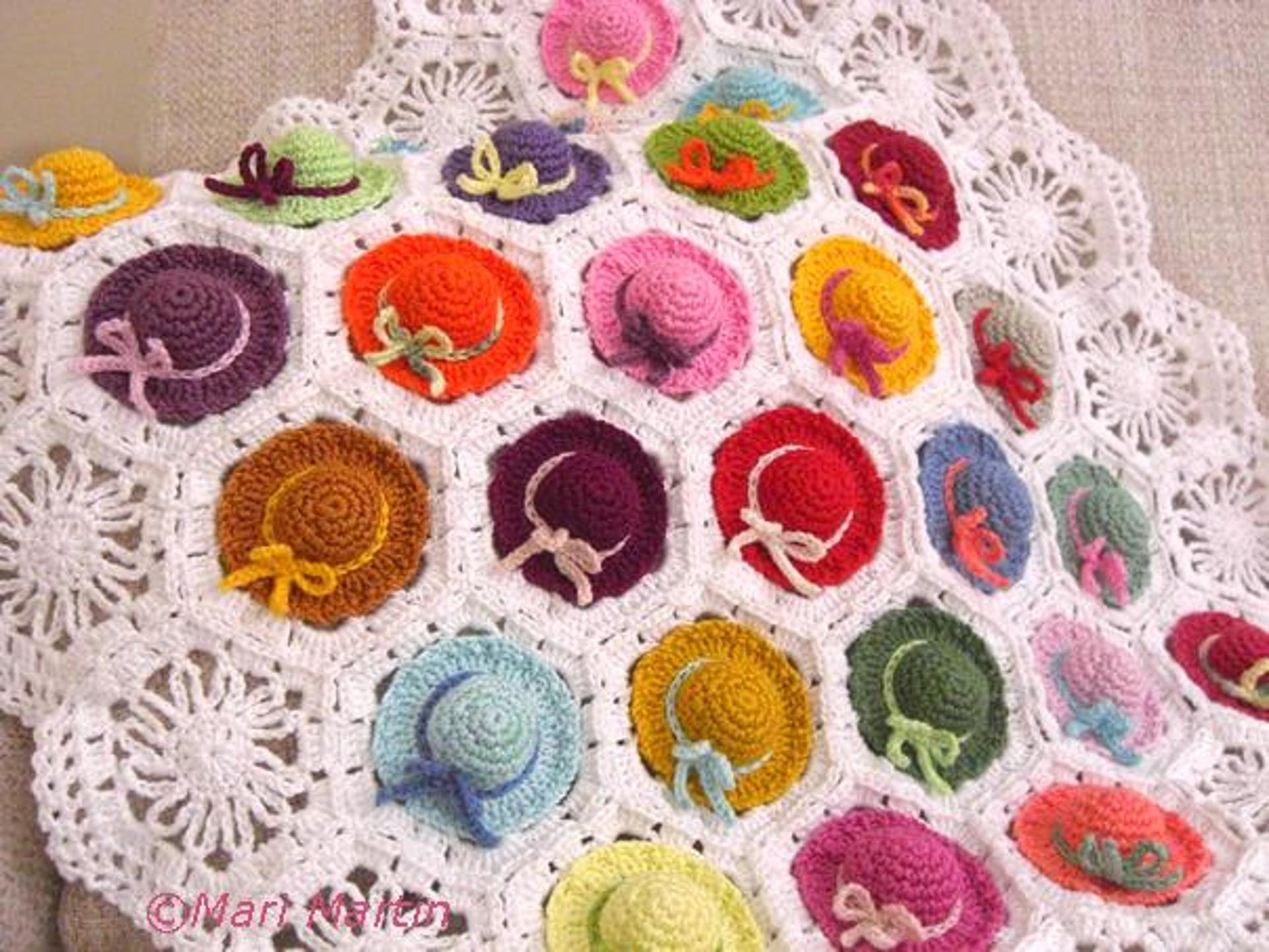 colorful crochet baby blanket with mini hats