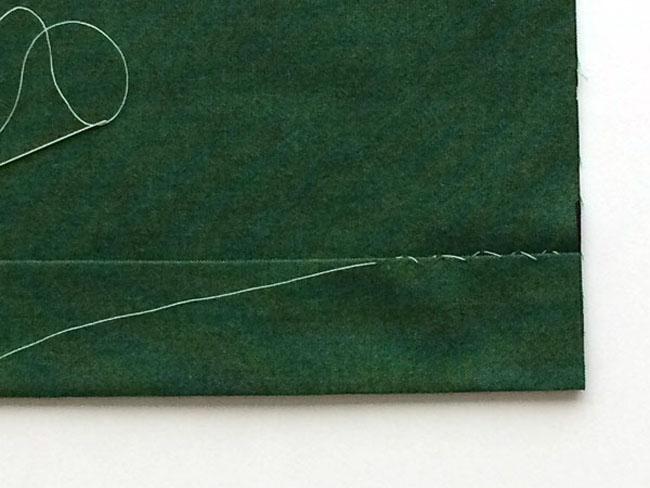 hemming-stitch on green wool