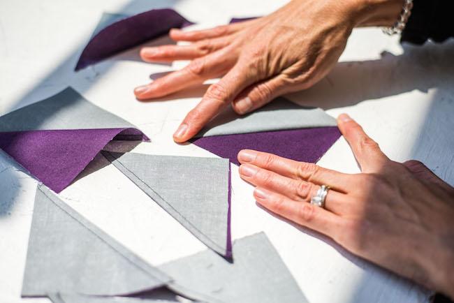 finger pressing a gray and purple half square triangle