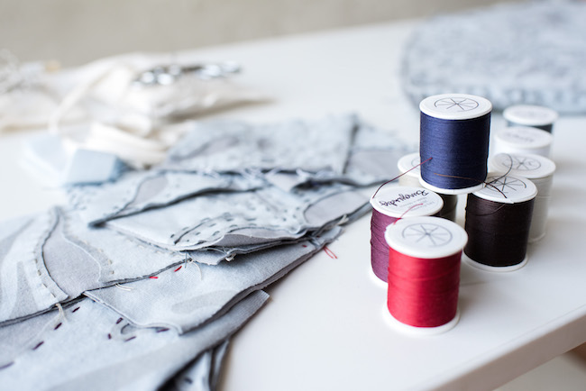 Spools of Thread and hand sewn fabric