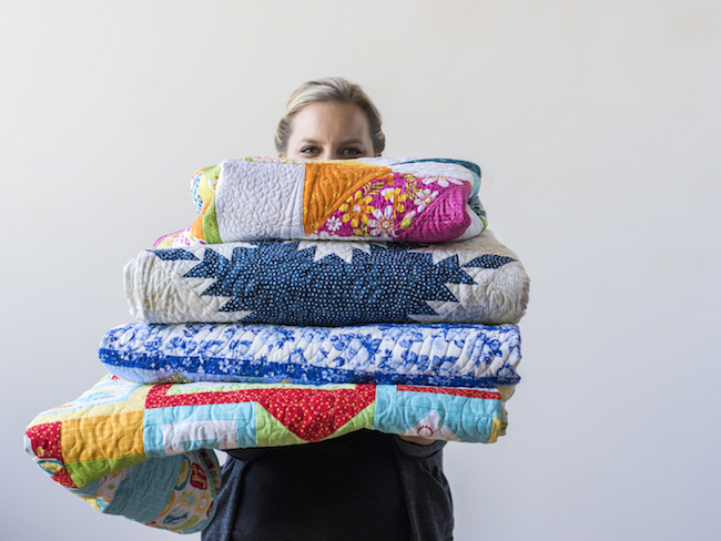 Angela Walters Holding a Stack of Quilts