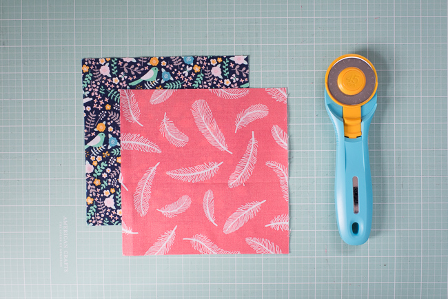 Two squares of fabric and rotary cutter