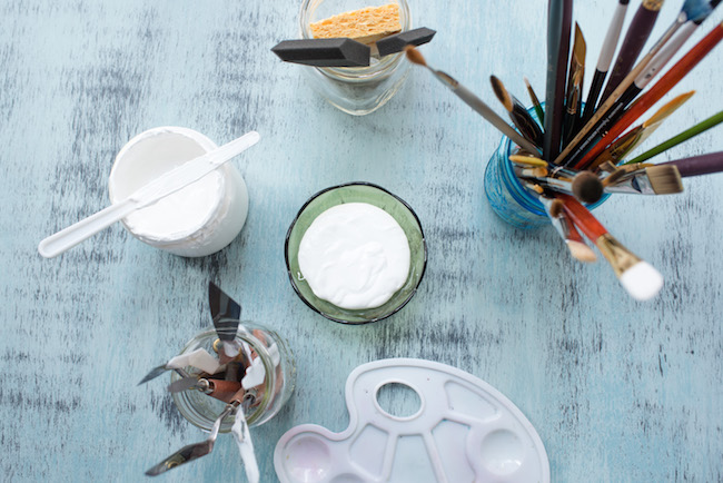 Painting Supplies arranged around bowl of white gesso